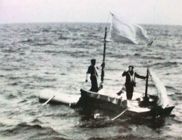 Small image of the two men on a simple life raft, standing to attract the attention of the rescue ship.