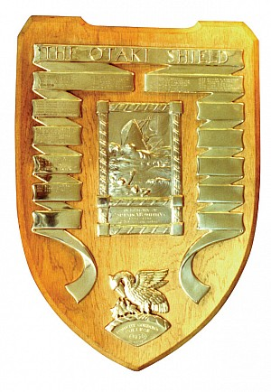 A wooden shield with silver detail listing the names of winners of the Otaki Scholarship