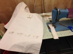 An unstuffed tabard-style vest next to a sewing machine