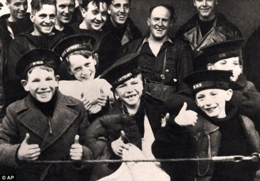 Smiling children in sailors hats on board a ship after rescue